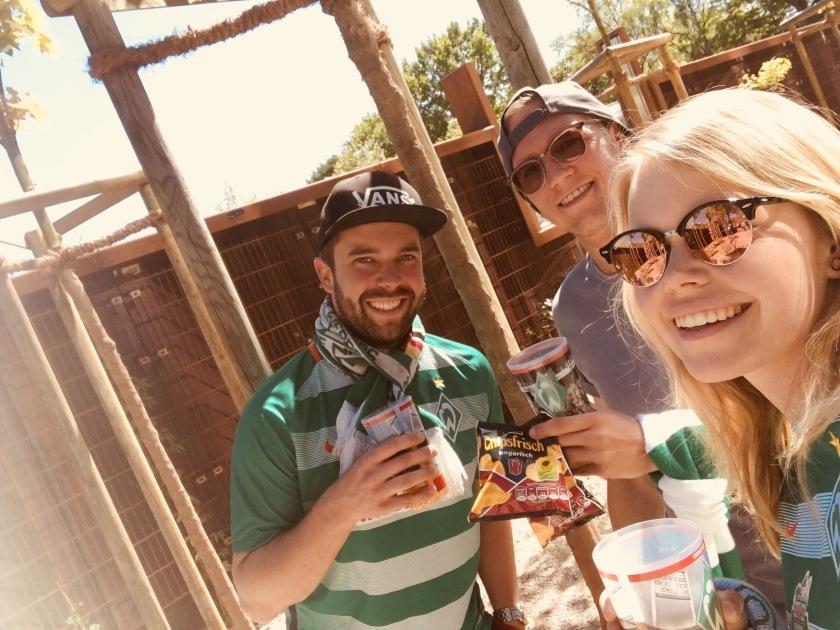 Drei Werder Fans stehen vor dem Stadion mit einem Becher Bier in der Hand und genießen das gute Wetter