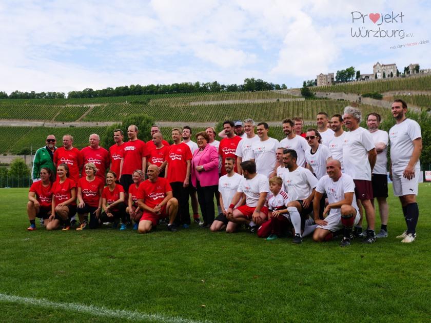 Gruppenfoto beider Mannschaften die für den guten Zweck Fußball spielen. Die Farben der Trikots in Rot und Weiß
