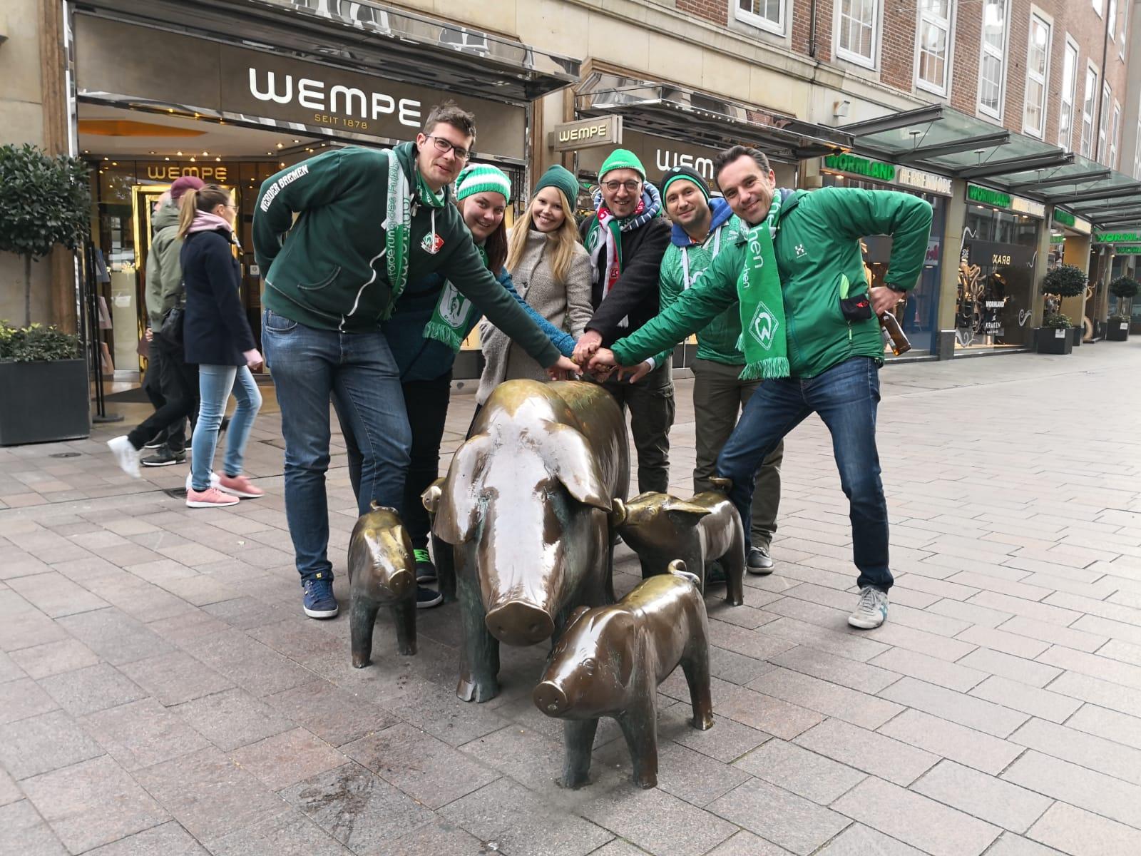 Werder Fans stehen vor den Schweinen der Sögestraße in Bremen