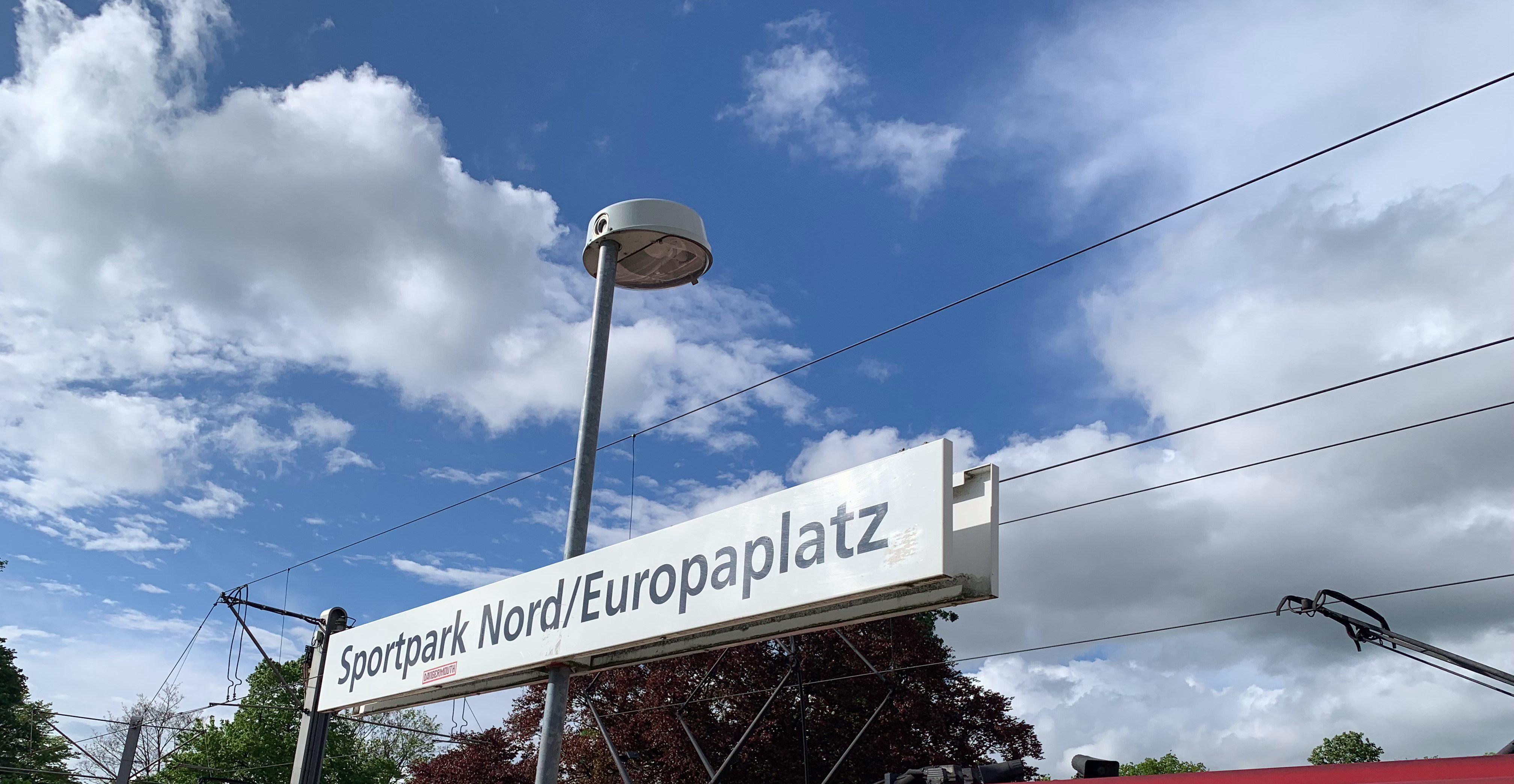 Schild im Vordergrund mit der Aufschrift: Sportpark Nord/Europaplatz