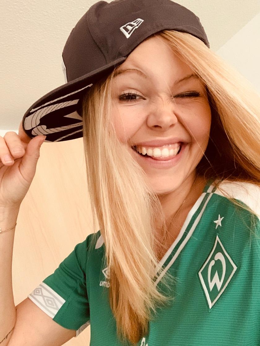 Nadine mit einem frechen Gesichtsausdruck im Werder-Trikot und Werder-Cap