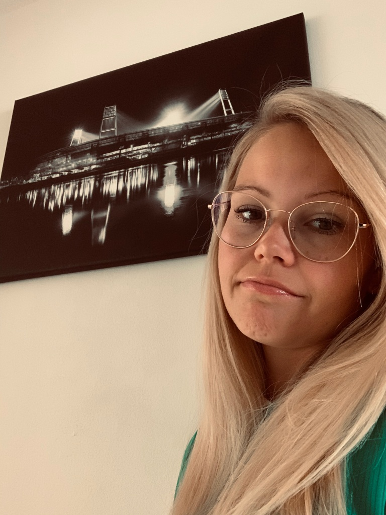 Nadine steht vor einem Bild auf dem das Weserstadion in schwarz/weiß abgebildet ist.